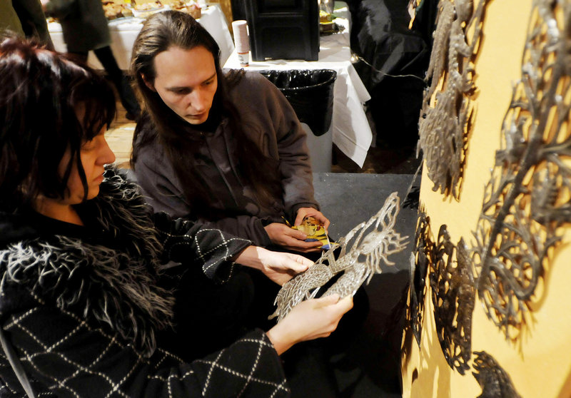 Erica Burkhart and Matiss Duhon, both of Portland, look over oil drum art pieces made in Haiti, during Konbit Sante s art sale on Saturday.