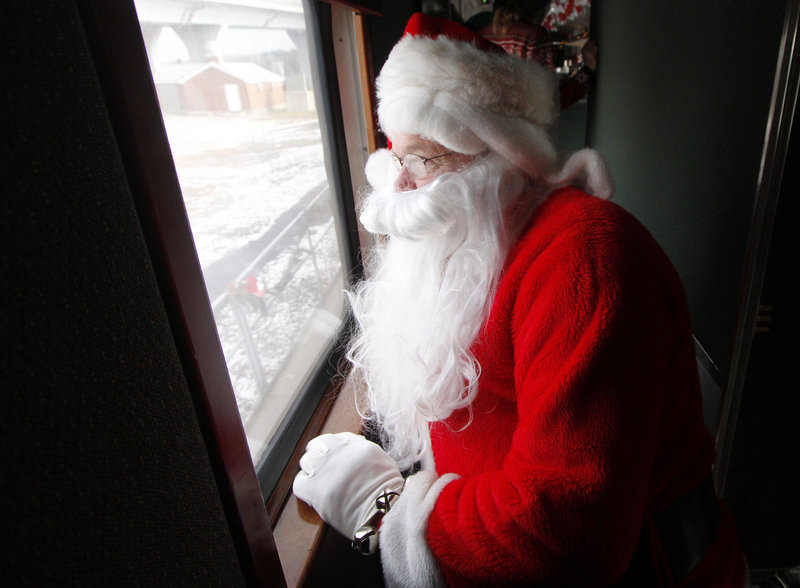 Santa Claus finds a quiet spot to watch the children board, so he can surprise them during the ride.