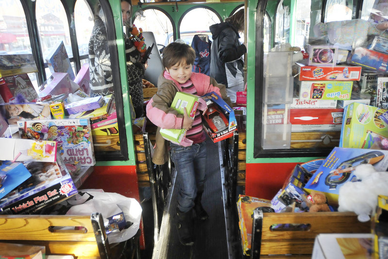 Mackenzie Rollins, 7, of Old Orchard Beach brings an armful of toys onto a Toys for Tots trolley as part of Saco Spirit's Holiday Festival on Saturday. Mackenzie came with her mother, Kim Rollins, who volunteered with a group from Prime Toyota in Saco.