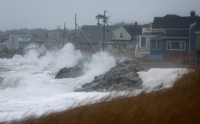 Waves break along Camp Ellis in Saco on Sunday, when a storm brought black ice to parts of Maine.