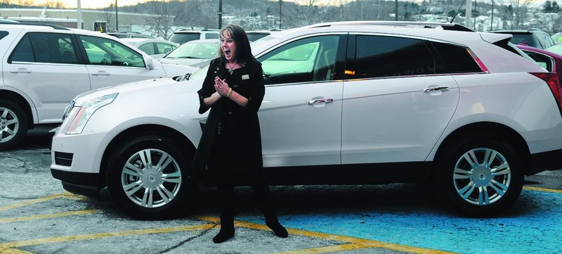 Julie Peacock of West Gardiner celebrates last week at O'Connor Motors in Augusta while picking up her sixth free car as an independent sales director for Mary Kay cosmetics.