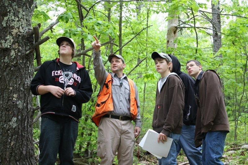 Lake Region High School students and Ken Canfield, pointing, of the Maine Forest Service study the Mayberry Hill Preserve, a 160-acre tract in Casco, during a trip last year.