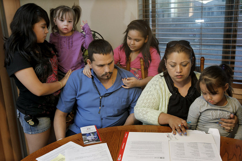 Francisco Felix, 32, is surrounded at home in Laveen, Ariz., by his family – daughters Carmen, 12, Carla, 2, Jessica, 10, Jennifer, 3 1/2, and his wife, Flor, as they fill out paperwork for the National Transplant Assistance Fund. In November, Francisco had been ready to get a lifesaving liver transplant, but had to cancel the surgery when the family could not raise the $500,000 needed. Flor is one of dozens of Arizona patients who need liver transplants but can't get them because of budget cuts to the state's Medicaid system.