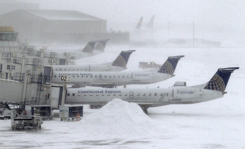 Blowing snow obscures Continental Express jets at their gates Monday at Cleveland Hopkins International Airport. Ohio airports reported scattered delays and cancellations due to a winter storm that has pummeled a broad area of the Midwest.