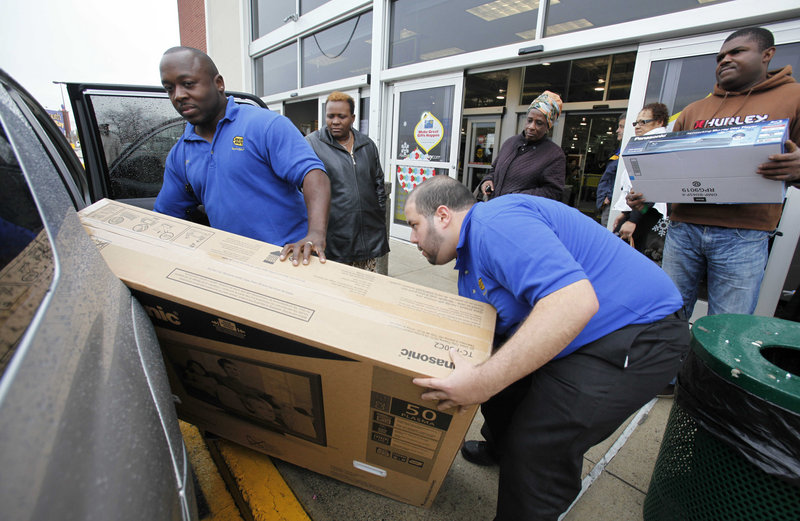 Two employees at a Best Buy in Boston help customers load a television into a car. The nation's largest electronics chain said its quarterly net income fell as it lost sales of laptops and televisions to competitors.