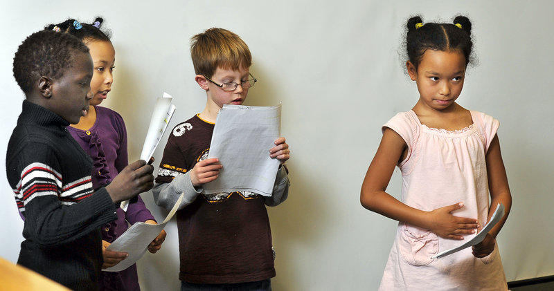 """Kiah Alexis, 7, pats her tummy to show hunger as fellow cast members, from left, Mattew Oryem, 8, Kiah's twin sister Kiana, and Jacob Bouchard, 8, all in second grade, read lines from """"Stone Soup"""" during an exhibition at Riverton School."""