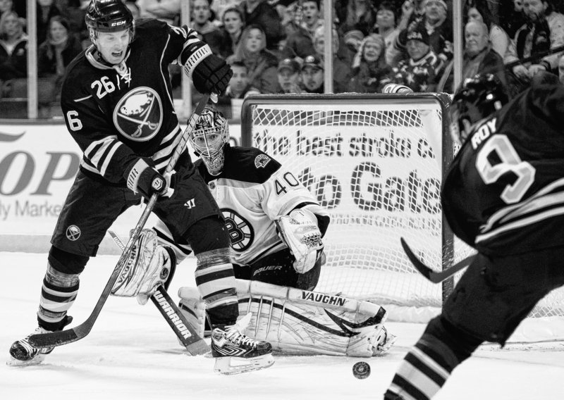 Boston goalie Tuukka Rask keeps his eye on the puck after a shot by Buffalo's Derek Roy, right, as Thomas Vanek fights for the puck during the Sabres' 3-2 win.