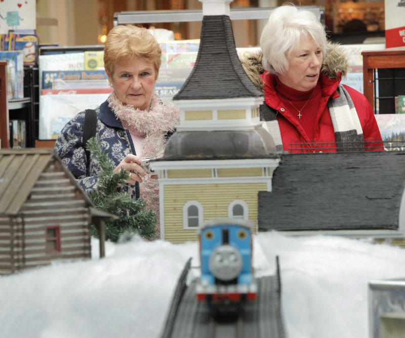 "Gail Domin of Old Orchard Beach, left, and Shari DeKoning of Scarborough look over the extensive train set-up at the Maine Mall on Wednesday. DeKoning reminisced about a train her brother got in 1948 – ""I loved it,"" she said."