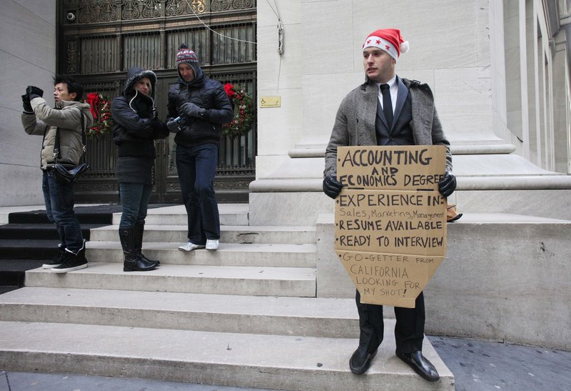 "Jesse Paloger holds up a job-seeking sign Wednesday on Wall Street; the bottom of his sign reads, ""Go-getter from California looking for my shot!"" Last week, initial claims for unemployment benefits dropped for the third time in four weeks."