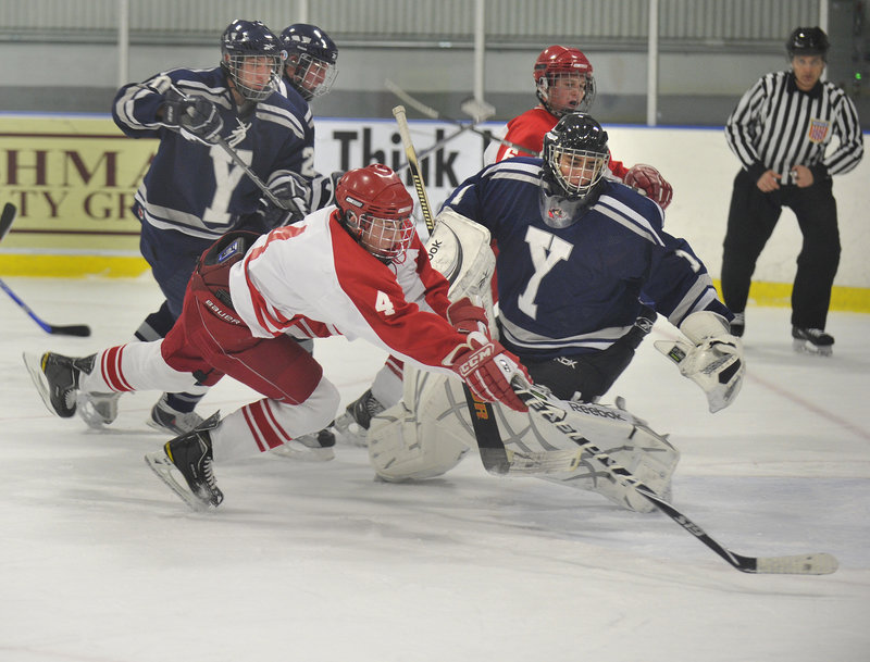 Robert Hannigan, who had two goals and three assists for South Portland, dives for the puck along with Yarmouth goalie Red DeSmith during their high school hockey game Thursday night at Portland Ice Arena. South Portland came away with a 7-0 victory.