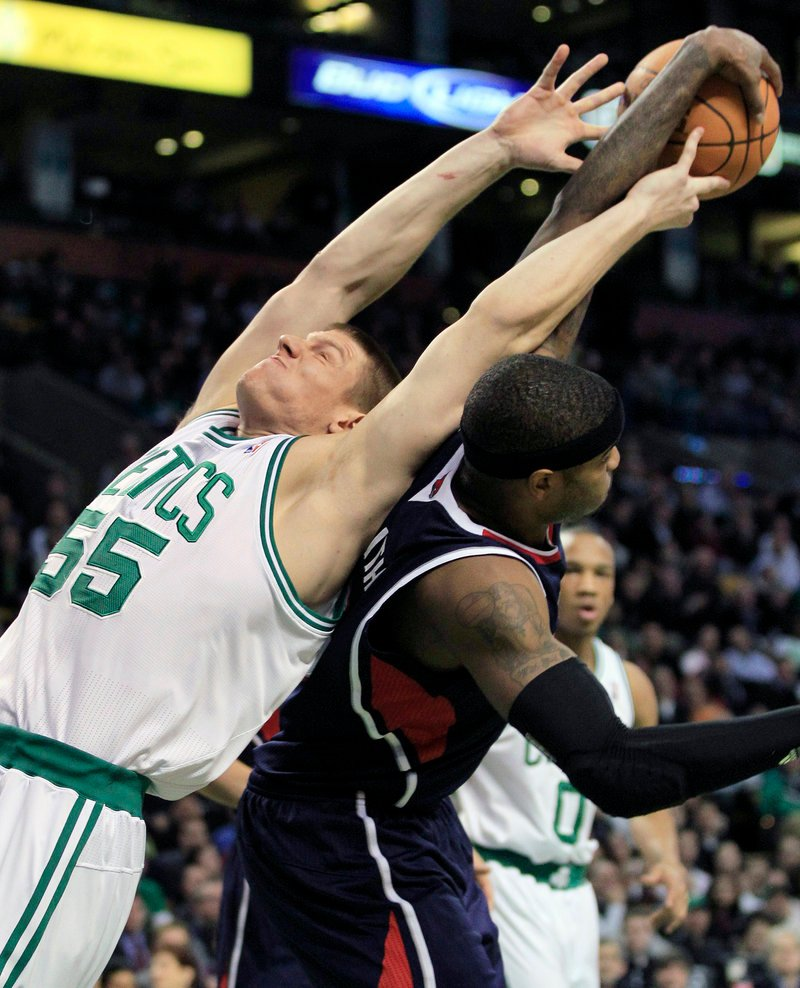 Luke Harangody of the Boston Celtics, left, gives it a stretch Thursday night but can't get a rebound away from Josh Smith of the Atlanta Hawks. The Celtics won, 102-90.