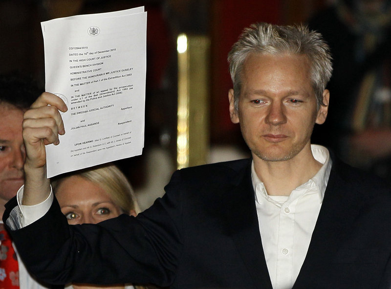 Julian Assange holds a court paper after being released on bail Thursday in London. Sweden is seeking his extradition for alleged sex crimes.