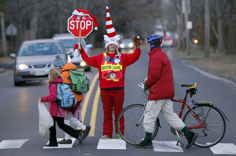 Crossing guard Lisa Green wears Christmas-inspired clothing as she brings the holiday spirit to her job Friday in Brunswick.