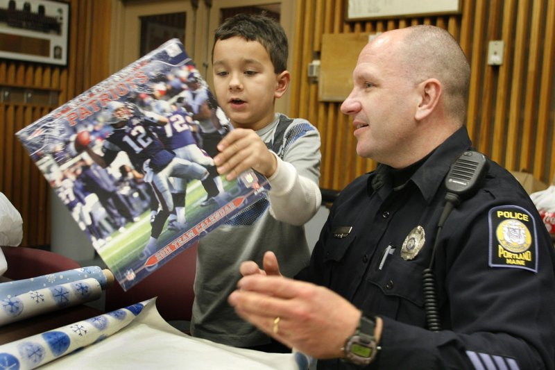 Seth Lehmus and Officer Les Smith wrap a calendar. Part of the department's focus is to create positive interactions with youths that pay off in good relationships later.