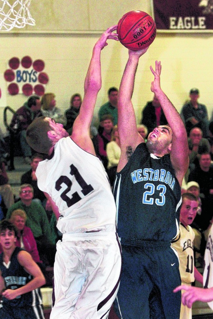 Jed Merrill, left, of Windham gets a hand on a shot by Edwin Grant of Westbrook in the second half of Westbrook s 61-50 victory Friday night, The Blazes led by 17 points in the second half, then had to hold off a late comeback.