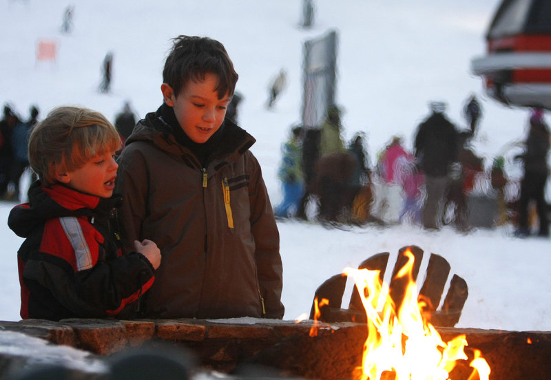 David, 5, and Peter Kane, 8, of Marblehead, Mass., warm up by the outdoor fire pit.
