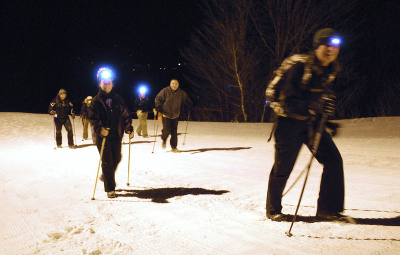 Susan Kilbride of Freeport, left, and Christine Clark of Portland, right, finish an hour-long full moon trek up Mt. Abram with other hikers on Dec. 18.