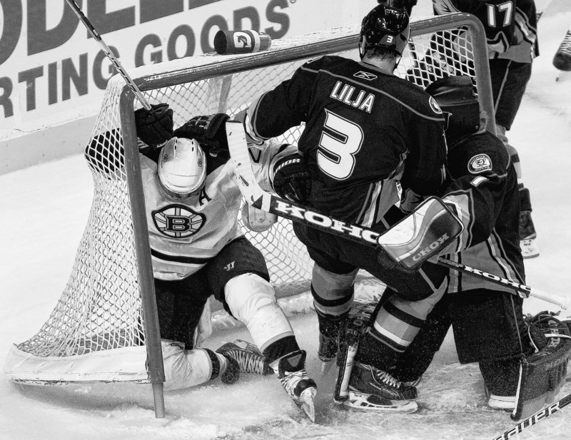 Mark Recchi, left, of the Bruins slides into the goal while chasing the puck ahead of Ducks defenseman Andreas Lilja during Monday night's game at Boston. Despite outshooting the Ducks in every period, the Bruins suffered a 3-0 loss.