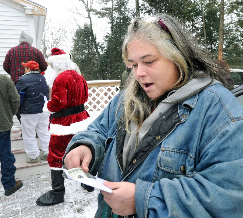 Patricia Ange is pleased by what she finds in an envelope given to her Tuesday when the Secret Santa paid a visit to the Warming Hut in Sebago to give away $100 bills. The benefactor plans to give away $20,000 this holiday season.