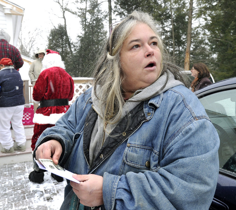 Patricia Ange at the Warming Hut in Sebago, opening her envelope from Secret Santa.