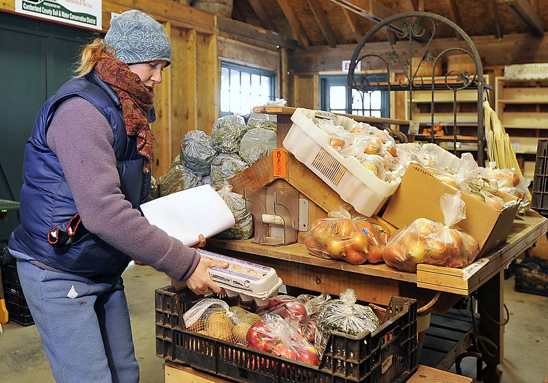 Mary Ellen Chadd of Green Spark Farm adds a dozen eggs to a crate of produce for a customer taking part in the Cape SoPo Winter Share online program. She was filling orders at the Jordan Farm on Wells Road in Cape Elizabeth.