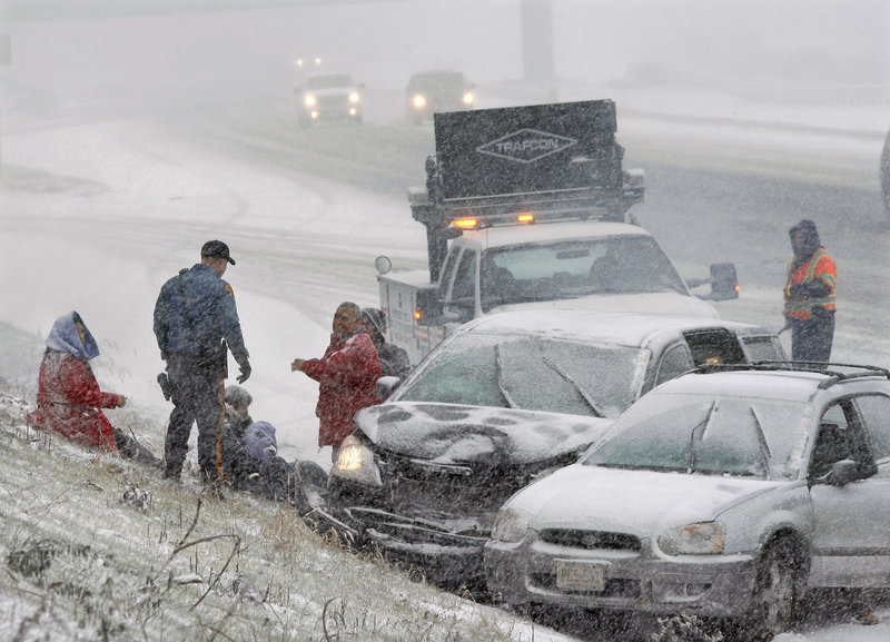 A New Jersey state trooper arrives to assist people after their cars collided in a heavy snowfall Sunday on Interstate 295 near Columbus, N.J.