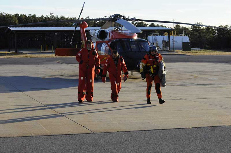 U.S. Coast Guard rescue swimmer Randall Rice escorts rescued mariners from a HH-60 Jay Hawk Rescue Helicopter at Air Station Cape Cod, Dec. 7, 2010. The mariners were rescued after the sailing vessel Raw Faith became disabled 100-miles