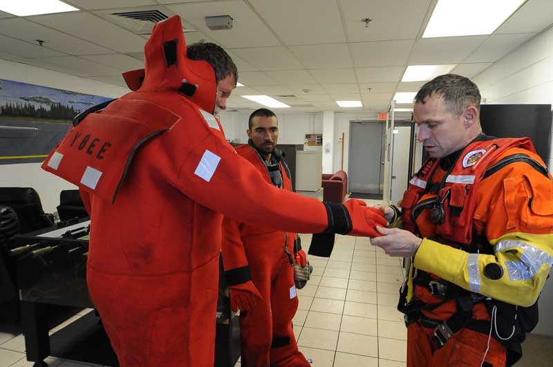 U.S. Coast Guard rescue swimmer Randall Rice help a rescued mariner remove his submersion suit at Air Station Cape Cod, Dec. 7, 2010. The mariners were rescued after the sailing vessel Raw Faith became disabled 100-miles southeast of Nantucket, Mass. U.S. Coast Guard photo by Petty Officer 3rd Class Luke Clayton.