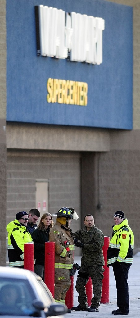 Three Augusta firefighters/paramedics and three unidentified people stand in front around 4 p.m. Thursday after the Augusta Walmart Supercenter was evacuated.