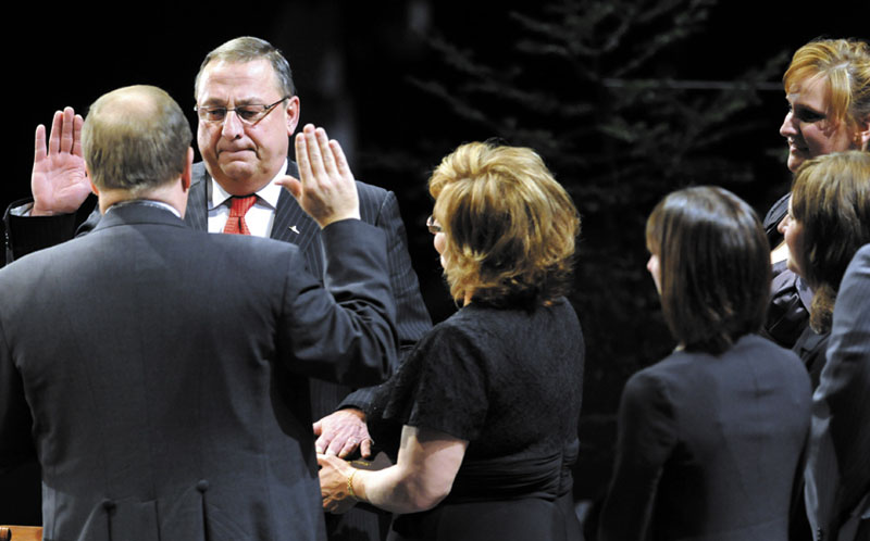 Gov.-elect Paul LePage takes the oath of office today from Senate President Kevin Raye, R-Perry, as wife Ann LePage holds the Bible and their children watch at the Augusta Civic Center.