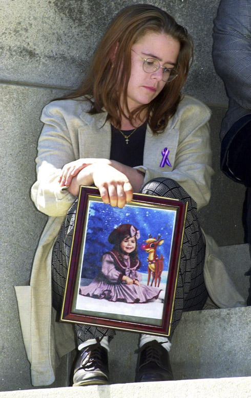 In this April 23, 2010 photo, Christy Baker sits outside the State House in Augusta following a news conference. She holds a photo of her daughter, Logan Marr, 5, who died on Jan. 31, 2001, while in foster care.