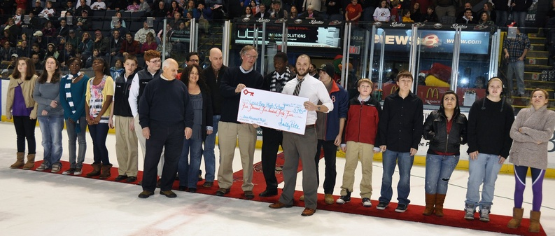 Zachary Davis, right, vice president of ticket sales for the Portland Pirates, presents a $5,425 check to Casco Bay High School Principal Derek Pierce between periods of Saturday's game between the Pirates and Providence Bruins. Students from Casco Bay High's Junior Achievement Program created a logo, developed a business plan and finalized a mission statement and vision for the game.