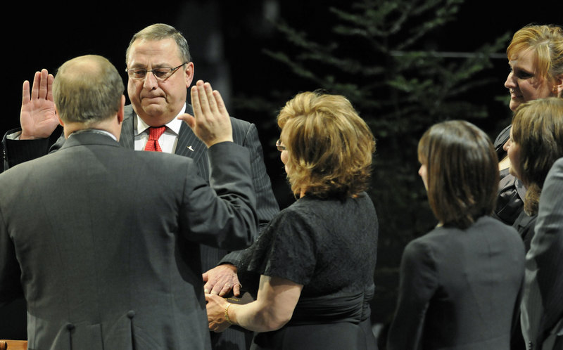 Paul LePage takes the oaths of office at the Augusta Civic Center Wednesday as his wife holds a family Bible.