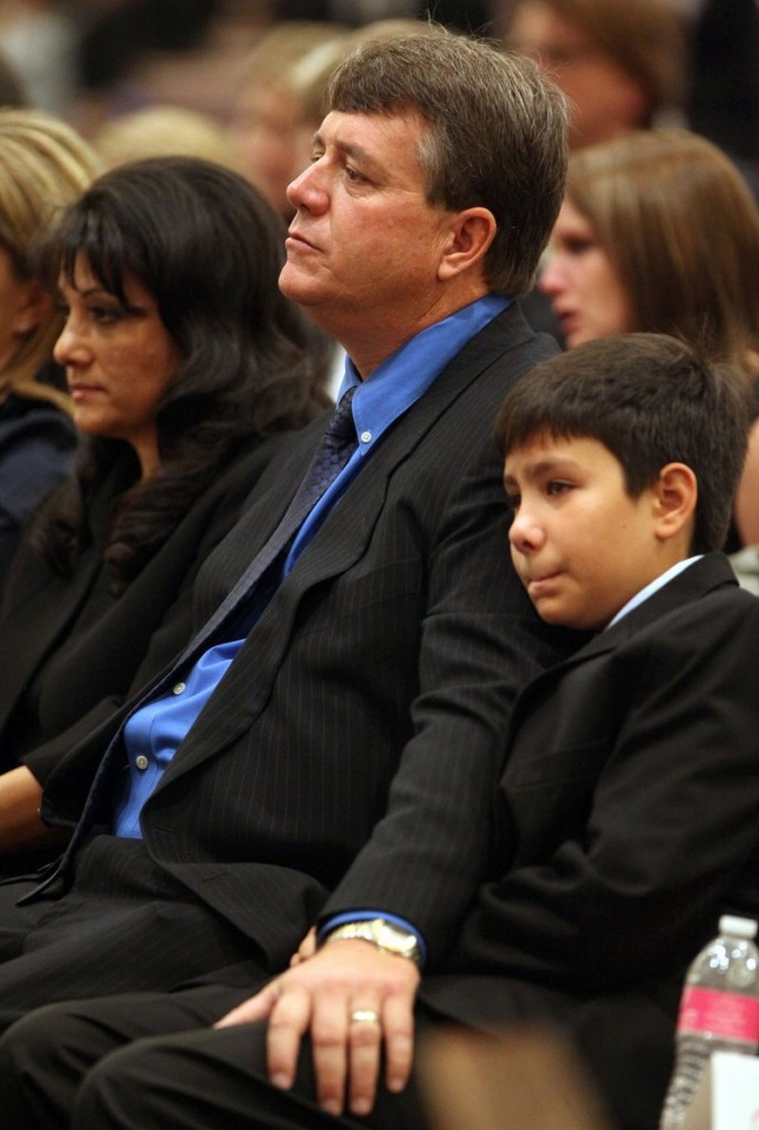 John Green rests his hand on his son Dallas' leg during the funeral of his daughter, 9-year-old Christina Taylor Green, on Thursday in Tucson, Ariz. Christina Taylor Green, the youngest victim of Saturday's shooting in Tucson, was felled by a gun with a 33-round magazine fired by Jared Loughner.