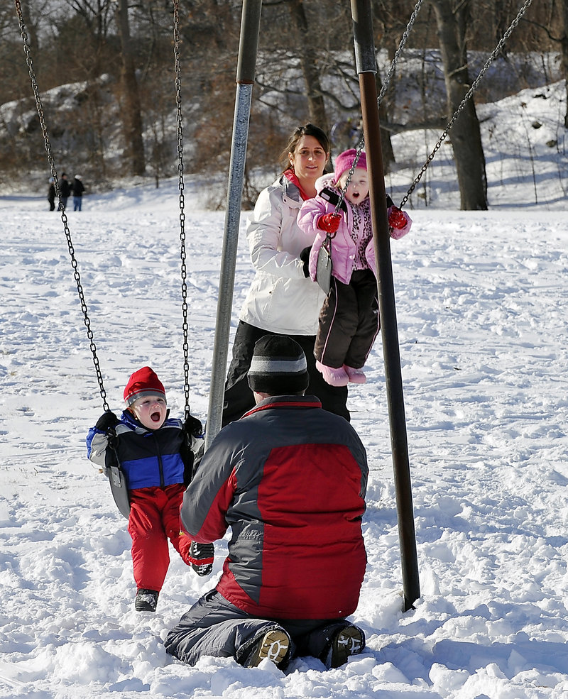 Matt Marks and his wife, Sandi Story, of South Portland take a break from sledding to push Aidan, 2, and Abby, 4, on the swings at Fort Williams.