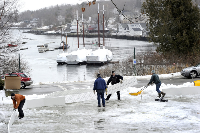 Community volunteers put up the sideboards and clear snow while building an ice rink from a kit in Camden Harbor Park on Jan. 19. The rink is located next to the town library and opened for free public use last week.