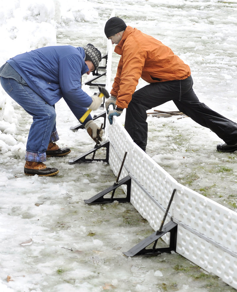 Jim Heard and Roy install brackets while putting the rink together with other volunteers.