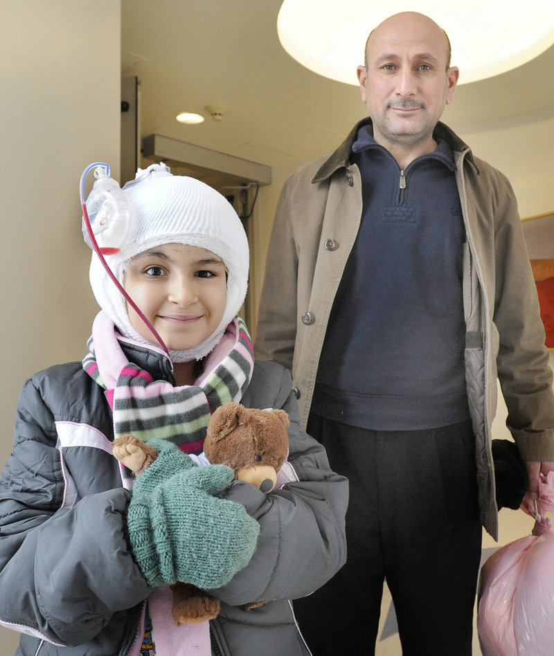 Noora Abdulhameed and her father, Afef, leave Maine Medical Center on Friday. The Iraqi 9-year-old has had 14 surgeries in this latest, and possibly last, trip to Portland.