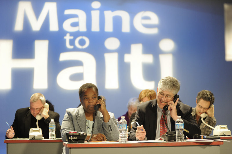 """Portland City Councilor Jill Duson and Mayor Nicholas Mavodones volunteer to accept donations during the """"From Maine to Haiti, One Year Later,"""" telethon at the WGME-TV Channel 13 studio in Portland on Friday."""