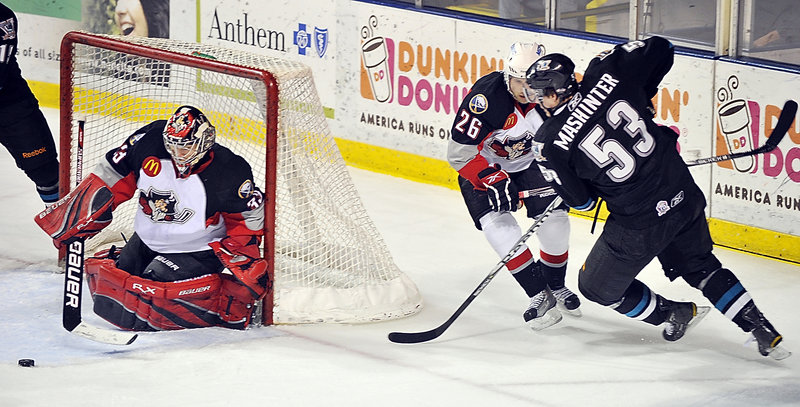 Pirates goalie David Leggio keeps his eye on the puck as Brandon Mashinter of Worcester sends it into the crease. Maxime Lagault defends.