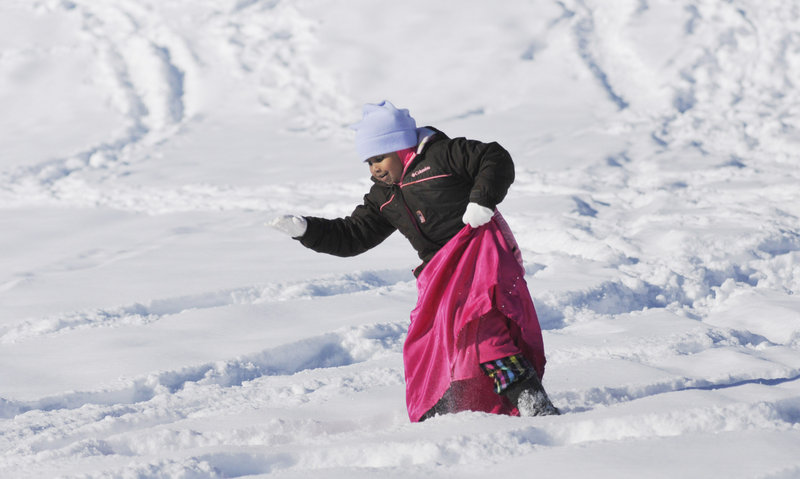 Amal Salaad, 5, of Portland, whose family is from Somalia, takes a careful step in the snow while wearing snowshoes at Payson Park in Portland as part of Saturday's WinterKids event. The Welcome to Winter Festival drew about 300 people to Payson Hill.