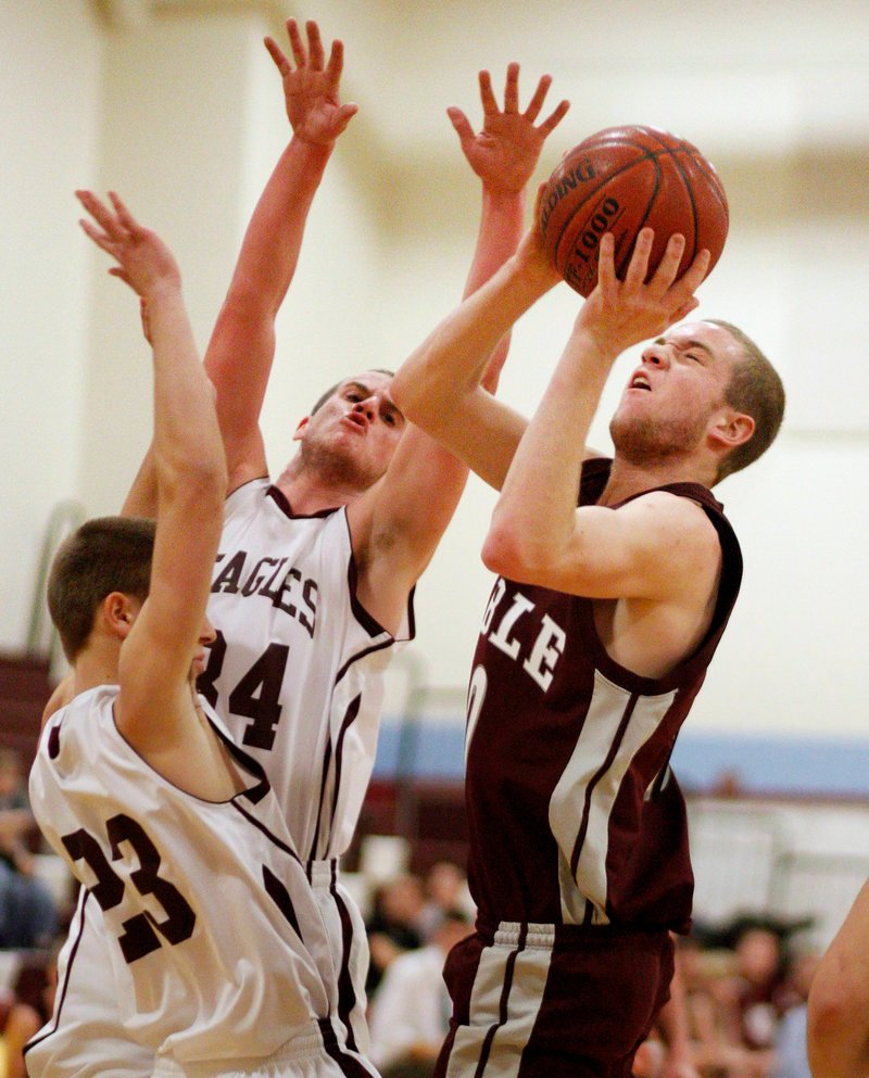 Mitch Edmunds of Noble gets off a shot Saturday while guarded by Ben Noble, left, and Kyle Williams of Windham. Edmunds scored 26 points as Noble came away with a 60-39 victory at Windham.