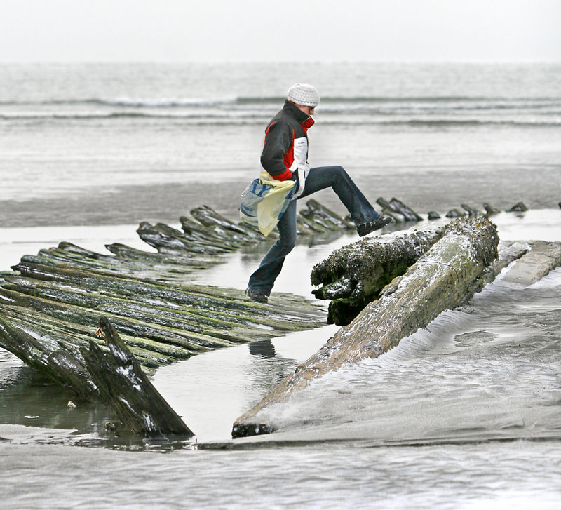 Gaella Materne of Portland walks on the remains of the schooner Howard W. Middleton, which sank in 1897, as she picks up trash during the Surfrider Maine Higgins Beach cleanup.
