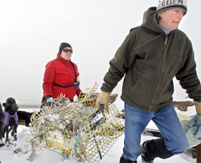 Sarah Mosley of Westbrook and Iver Carlsen of Scarborough, members of the Surfrider Maine Foundation, remove a lobster trap during a cleanup at Scarborough's Higgins Beach on Sunday. The nonprofit group cleans a different beach each winter.