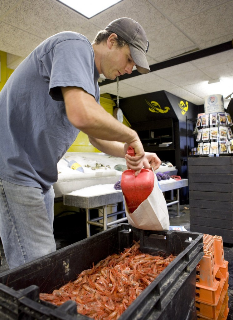 Keith Foley fills a bag with fresh Maine shrimp at Free Range Fish in Portland on Saturday. Organizers of the National Seafood Marketing Coalition say enhanced marketing efforts will strengthen the U.S. seafood economy and generate jobs.