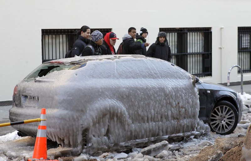 Pedestrians gawk at a car that was covered in ice after a water pipe broke Monday in New York. The city doubled the number of vans checking on homeless people due to the extreme cold.