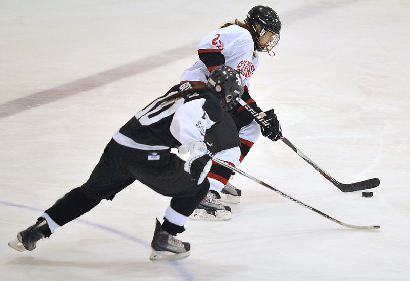 Kristina Block of Scarborough carries the puck through the neutral zone while being pursued by Sophie Goulet of St. Dom's.