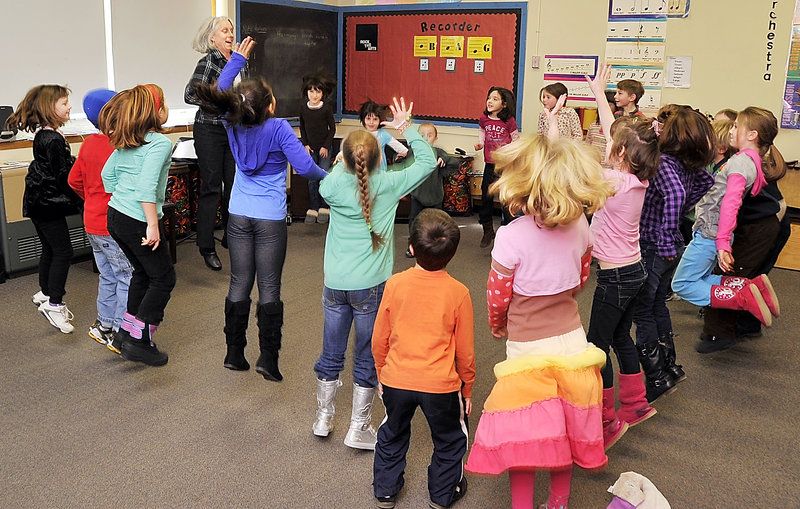 """Alyson Ciechomski, music teacher at Longfellow Elementary School in Portland, leads a lesson on musical elements like timing and rhythm as first- and second-graders jump to a classical """"Pop Goes the Weasel"""" orchestral instrumental with their teacher."""