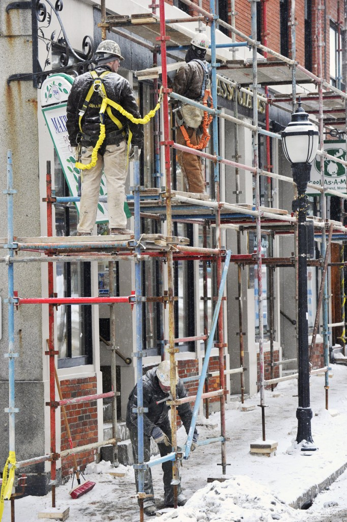 Construction workers with Gorham-based Knowles Industrial Services Corp. erect staging Tuesday in advance of an extensive restoration of the masonry on the building at the corner of Fore and Moulton streets in Portland. The project is expected to take about three months.