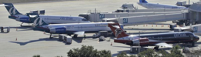 Three AirTran Airways jetliners sit at their gates last week at the Tampa International Airport in Tampa, Fla. U.S. airlines are in the midst of reporting fourth-quarter results that should cap the industry's first moneymaking year since 2007.